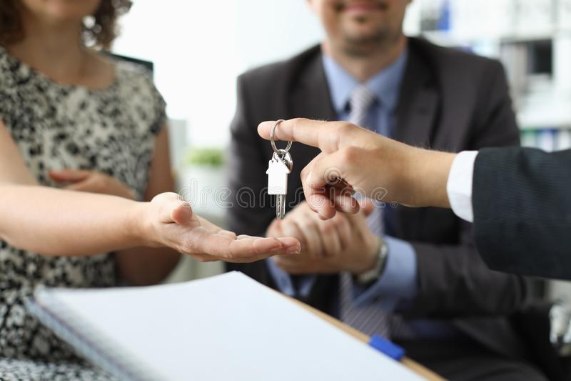 Mão da chave da casa da posse do corretor de imóveis contra o escritório foto de stock royalty free