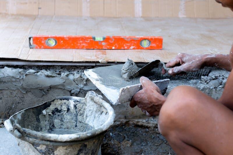 Mão da construção que guarda a pá de pedreiro que emplastra o concreto foto de stock