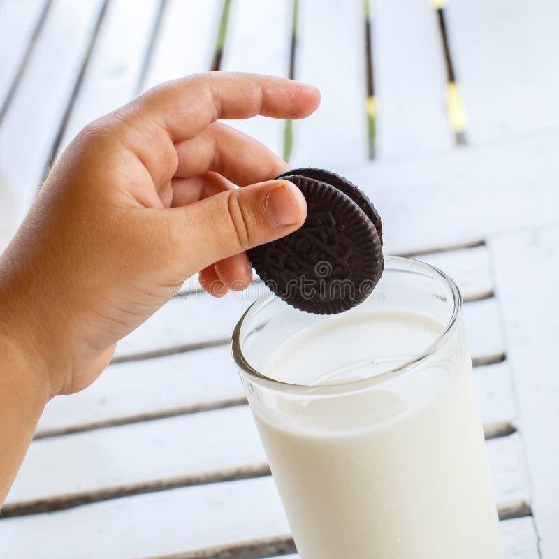 A mão da criança com cookies de Oreo estende ao leite fotografia de stock royalty free