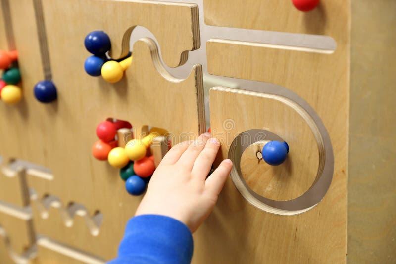 A mão da criança joga com enigma de madeira foto de stock royalty free