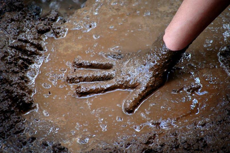 Mão da criança na lama e água que joga Muddy Wet imagens de stock royalty free