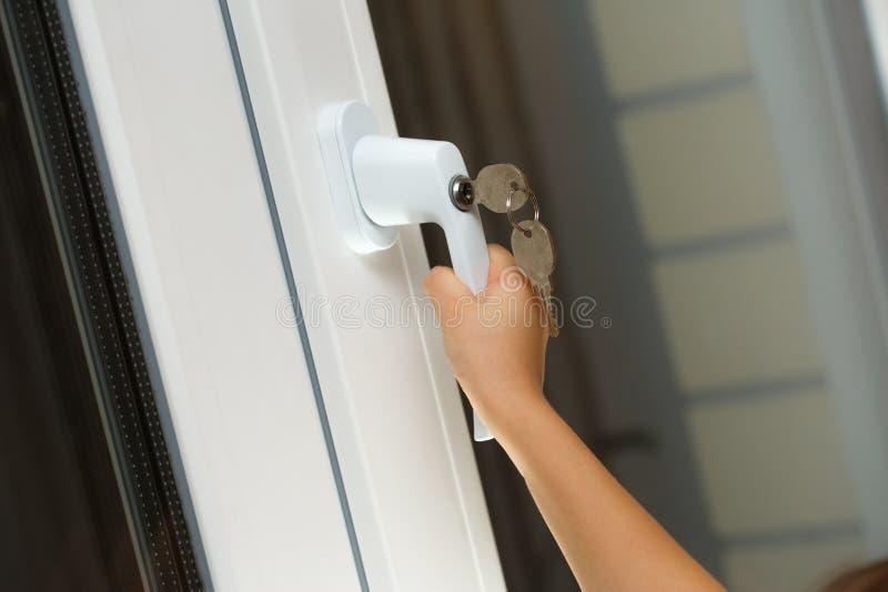 A mão da criança no punho de janela seguro foto de stock