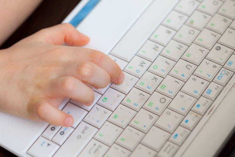 A mão da criança no teclado do portátil imagens de stock royalty free