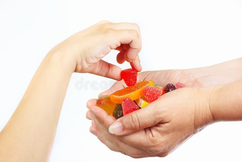 A mão da criança pega a geleia e os doces das mãos seu fim da mãe imagens de stock royalty free