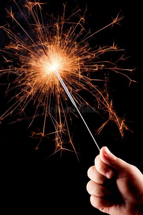Mão da criança, prendendo um sparkler ardente. fotografia de stock