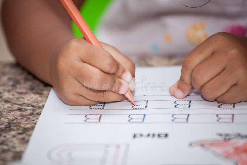 Mão da criança que escreve lhe trabalhos de casa fotos de stock royalty free