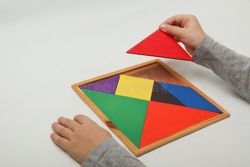 A mão da criança que guarda uma parte faltante em um tangram imagens de stock