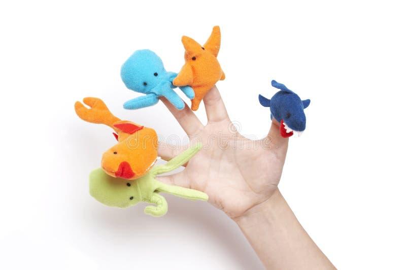 Mão da criança que joga com fantoches do dedo imagens de stock