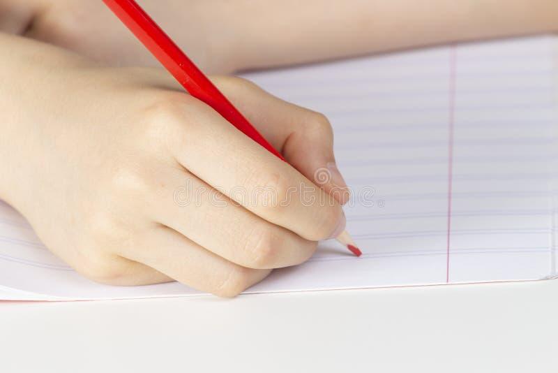 Mão da criança que mantém o lápis vermelho contra a página vazia do caderno fotografia de stock royalty free