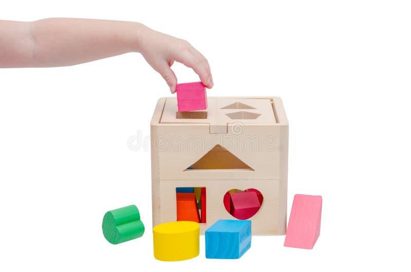 A mão da criança que põe a forma de madeira do brinquedo na caixa de madeira fotos de stock royalty free