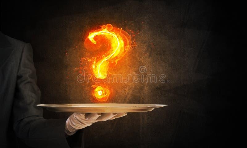 Mão da empregada de mesa que apresenta ponto de interrogação flamejante foto de stock