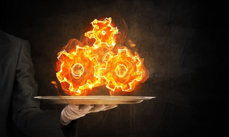 Mão da empregada de mesa que apresenta rodas denteadas flamejantes imagens de stock