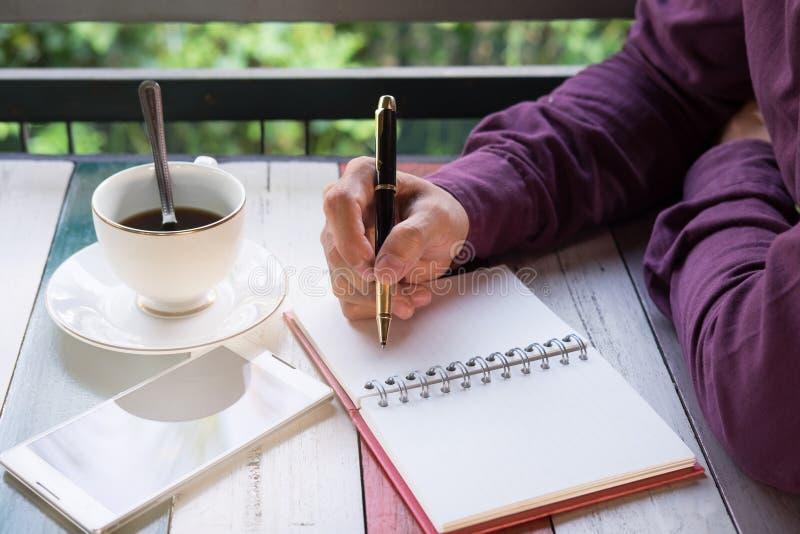 Mão da escrita da pena de terra arrendada do homem de negócio no papel do caderno Fron imagens de stock royalty free