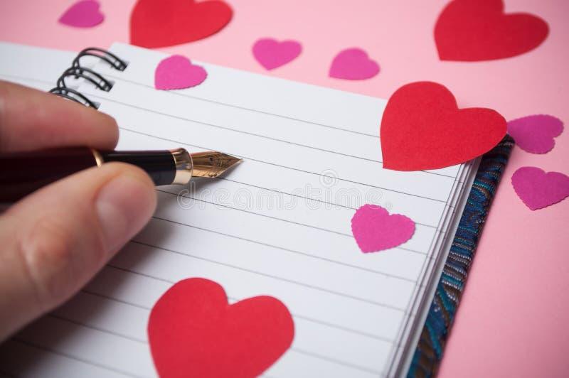 mão da escrita do homem com a pena do vintage no livro de nota dos spirales com corações de papel no fundo cor-de-rosa fotografia de stock