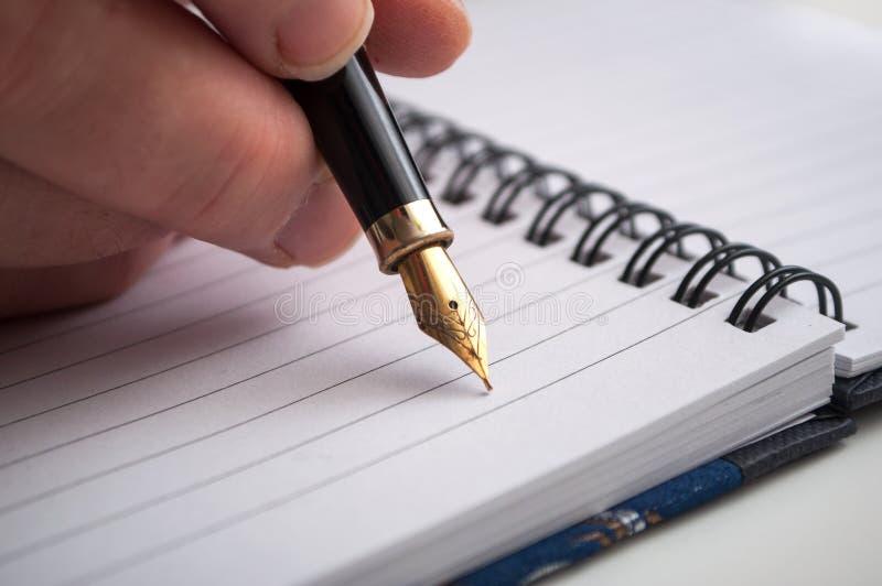 mão da escrita da mulher com a pena do vintage no livro de nota dos spirales no fundo branco foto de stock royalty free