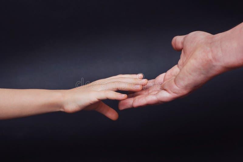 A mão da filha guarda a mão dos pais na obscuridade - fundo azul Conceito parental do relationshipp fotos de stock royalty free