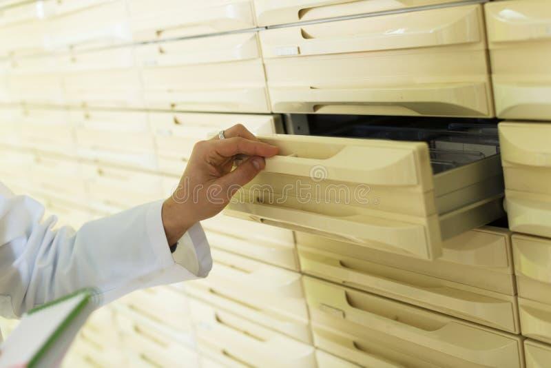 Mão da gaveta da abertura do pharmaceutist no farmacy imagem de stock
