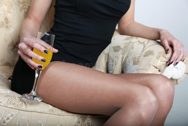 Mão da jovem mulher que guarda um vidro da bebida foto de stock royalty free