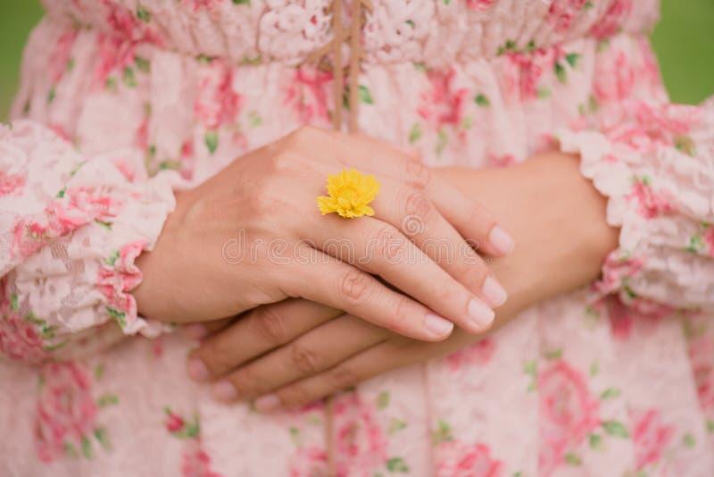 A mão da jovem mulher que veste a flor amarela representa da aliança de casamento fotos de stock royalty free