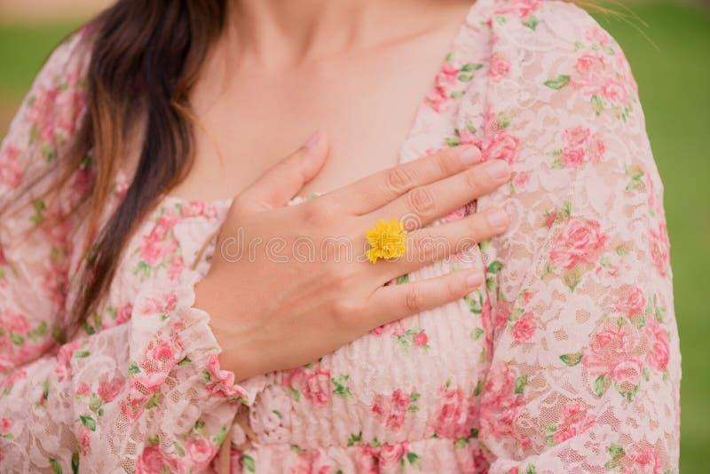 A mão da jovem mulher que veste a flor amarela representa da aliança de casamento foto de stock royalty free