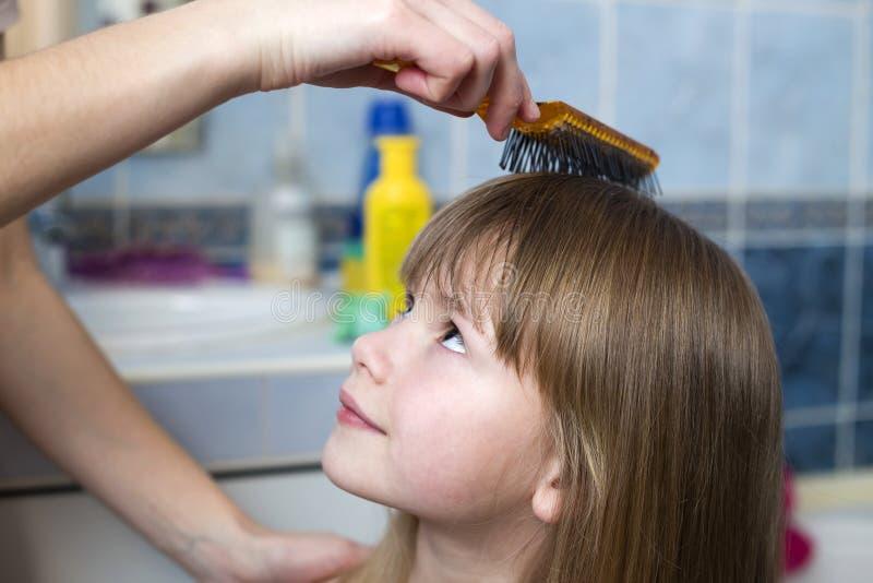 Mão da mãe com a escova que penteia o cabelo justo longo da menina bonito da criança após o banho no fundo interior borrado imagem de stock royalty free