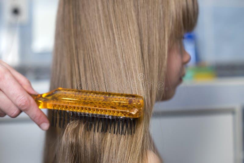 Mão da mãe com a escova que penteia o cabelo justo longo da menina bonito da criança no fundo interior borrado Retrato do perfil imagens de stock