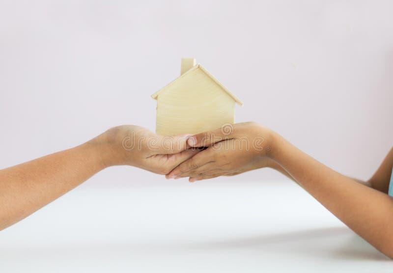 Mão da mãe dando o modelo de casa de madeira para a metáfora da filha o legado do conceito de propriedade selecione foco profun fotografia de stock royalty free