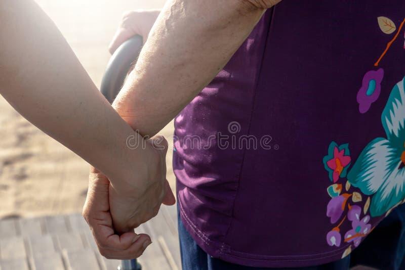 A mão da mãe da posse da filha ou do filho para ajudá-la a andar com cuidado imagem de stock royalty free