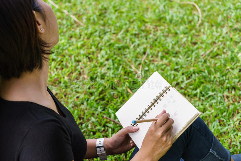 A mão da menina asiática pronta para escrever algo no caderno imagens de stock