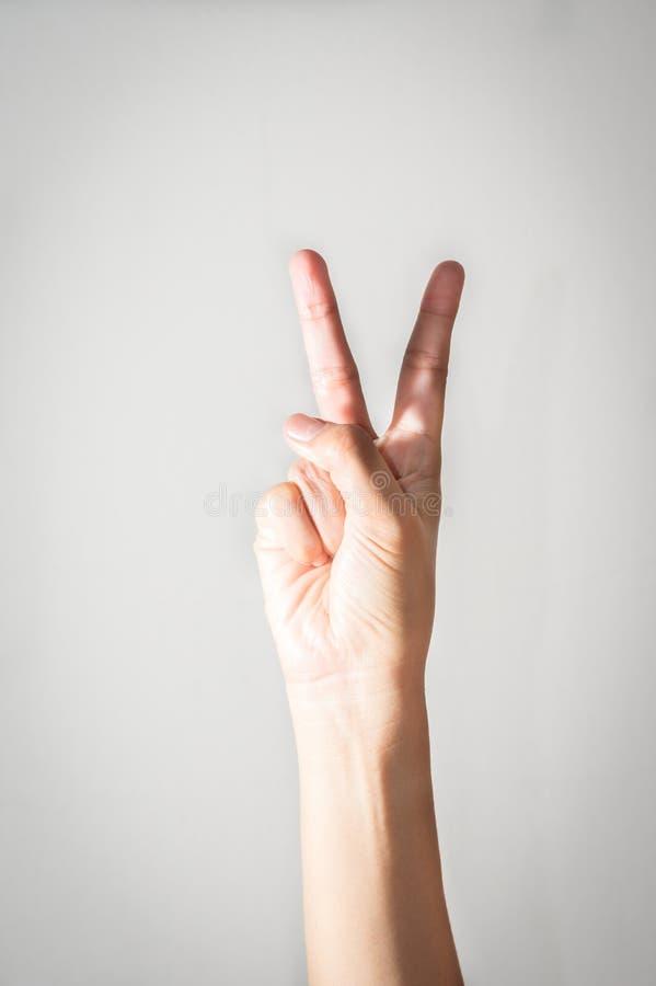 Mão da menina com dois dedos acima fotografia de stock
