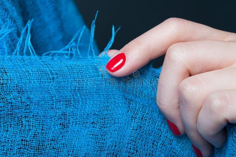 Mão da menina com o tratamento de mãos feminino que guarda o lenço azul imagens de stock royalty free