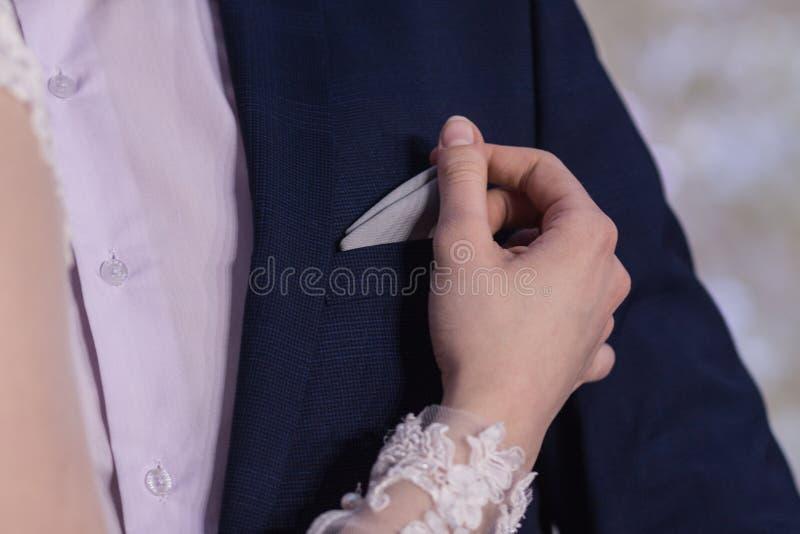 A mão da menina corrige ou retira um lenço no bolso de peito do casaco azul do ` s do homem Close-up fotografia de stock