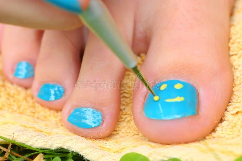 Mão da menina do adolescente com o pedicure da escova do laque do esmalte seu pé dos dedos do pé foto de stock