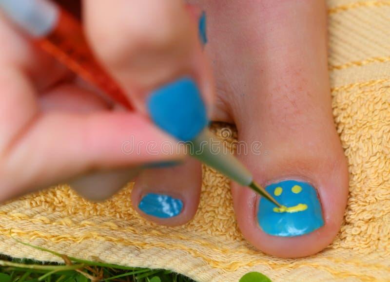 Mão da menina do adolescente com o pedicure da escova do laque do esmalte seu pé dos dedos do pé fotografia de stock