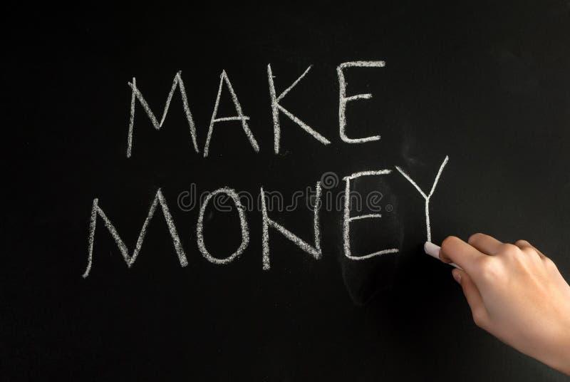 A mão da menina escreve a palavra faz o dinheiro com giz branco no quadro-negro imagens de stock