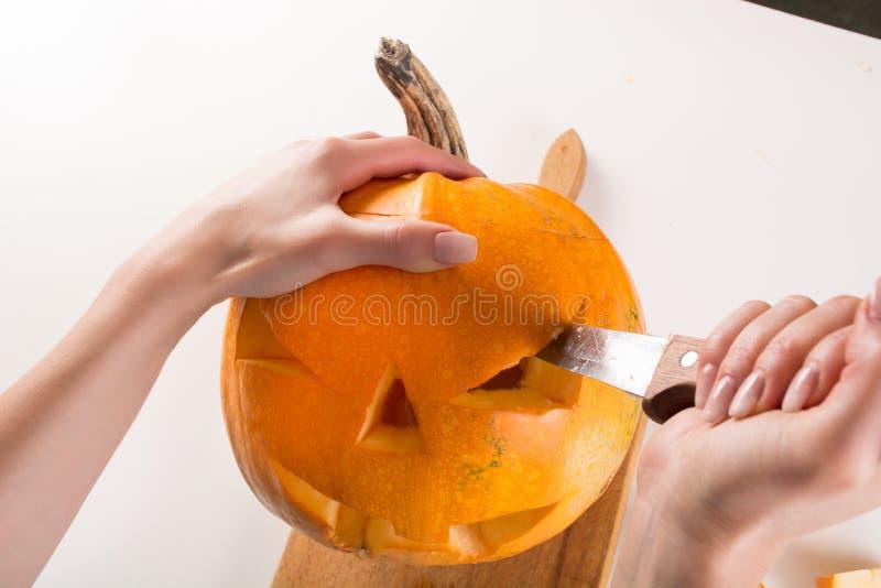 A mão da menina faz lanternas do jaque o para o feriado de Dia das Bruxas com faca de cozinha imagem de stock royalty free