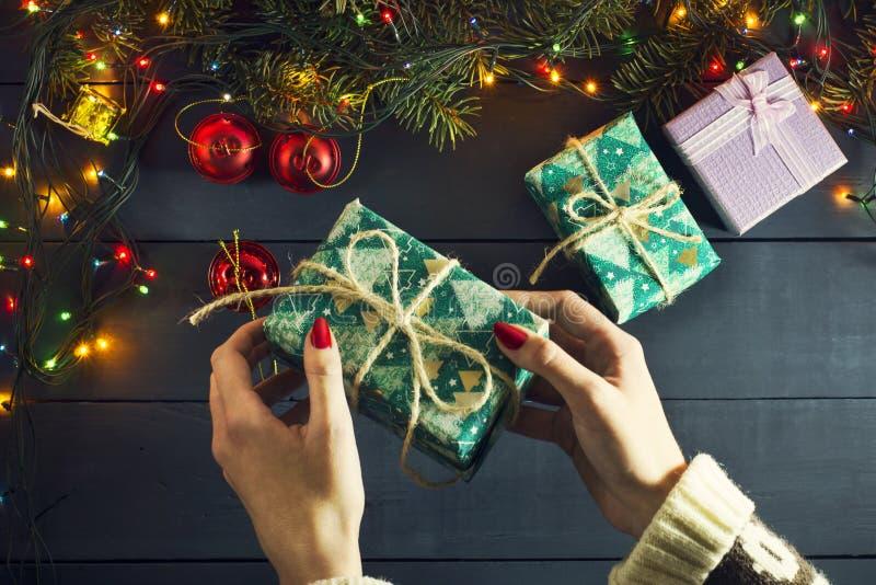 A mão da menina põe presentes sob a árvore de Natal Com festões luminosas Vista superior Ano novo Fundo do Natal fotos de stock royalty free