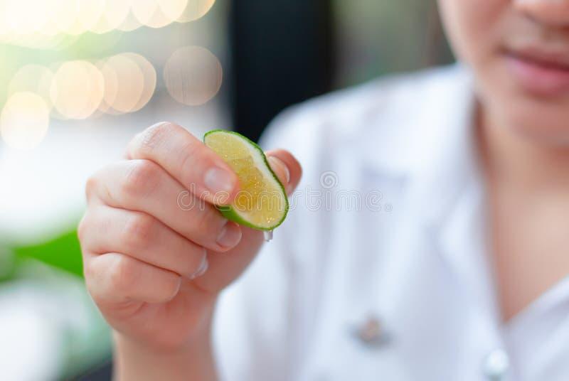 Mão da menina que espreme pouco suco de limão do cal imagens de stock