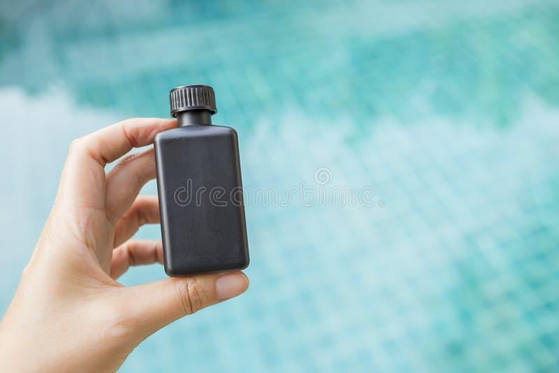 Mão da menina que guarda a garrafa plástica preta sobre o fundo azul borrado da água da piscina fotos de stock royalty free