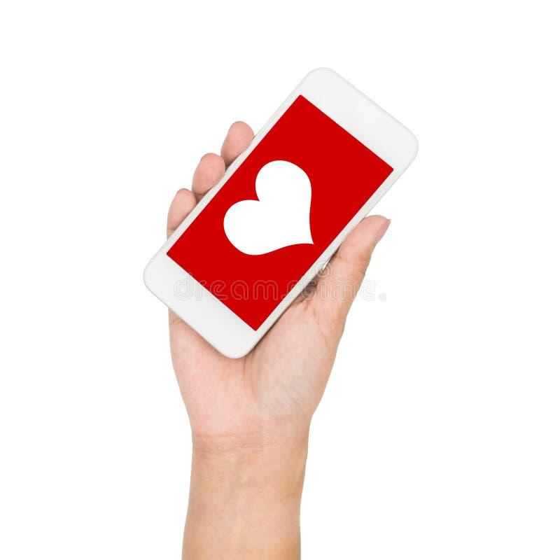 Mão da menina que guarda o coração da exposição do telefone celular na tela vermelha imagem de stock royalty free