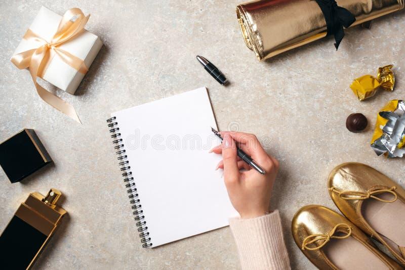 Mão da mensagem de texto da escrita da mulher no bloco de notas de papel vazio Tabela feminino com material elegante Mesa do espa foto de stock royalty free