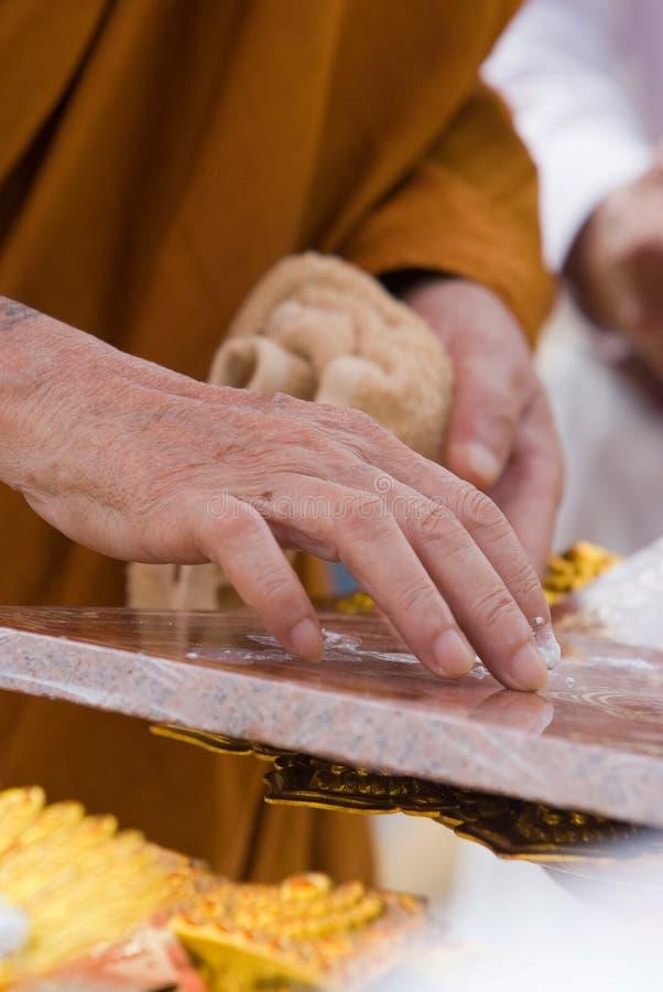 Mão da monge budista que pinta símbolos religiosos imagens de stock royalty free