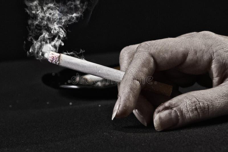 Mão da mulher adulta que prende um cigarro fotos de stock