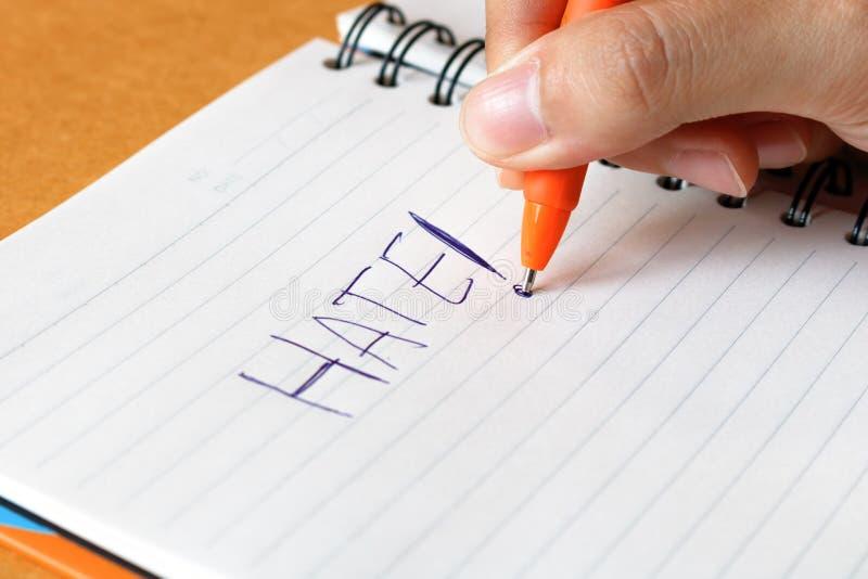 Mão da mulher com ódio da palavra da escrita da pena no bloco de notas fotografia de stock royalty free