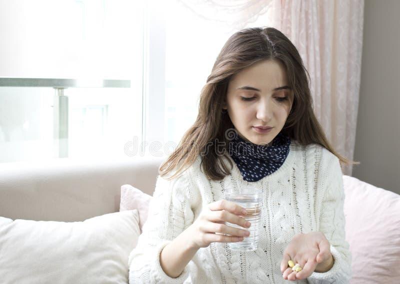 Mão da mulher com as tabuletas da medicina dos comprimidos e o vidro da água em suas mãos fotos de stock
