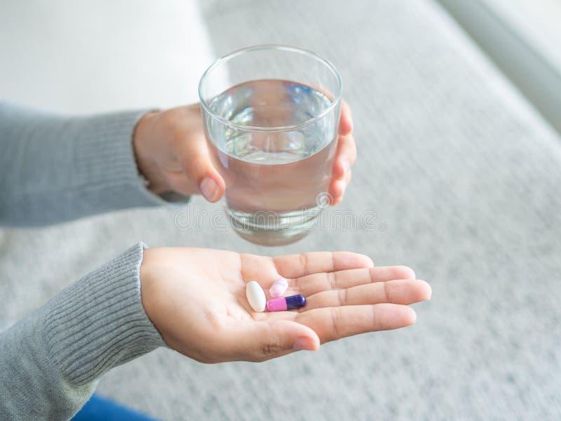 Mão da mulher com as tabuletas da medicina dos comprimidos e o vidro da água nela fotos de stock