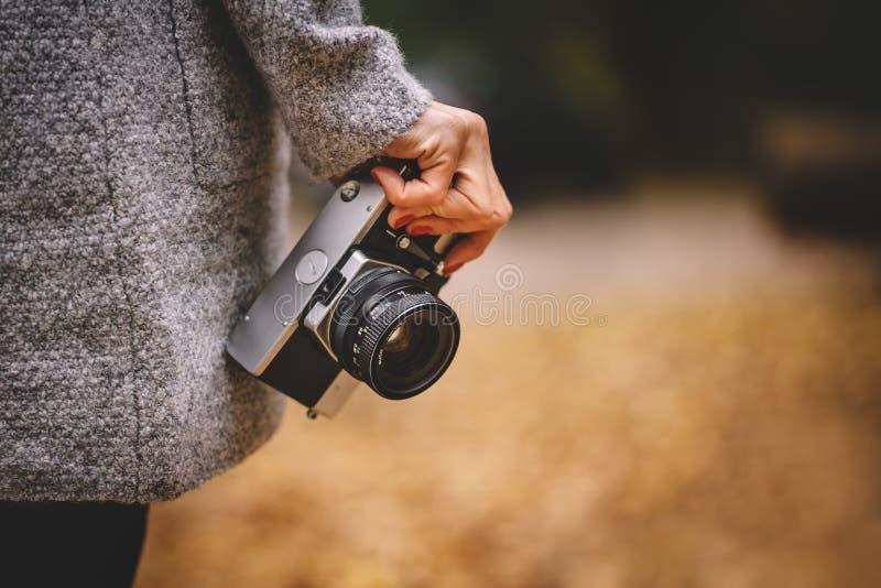 Mão da mulher com a câmera análoga retro do filme Conceito para o curso, desejo por viajar, aventura exterior Queda natural, defo fotografia de stock royalty free