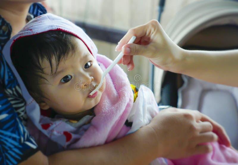 Mão da mulher com a colher que alimenta sua filha, uma posse chinesa asiática bonita doce e adorável do bebê por seu pai que tem  imagem de stock