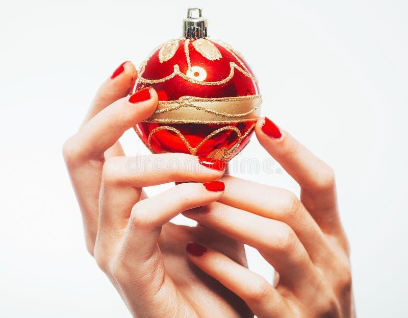 Mão da mulher com o brinquedo vermelho e o tratamento de mãos do ano novo no branco fotografia de stock royalty free