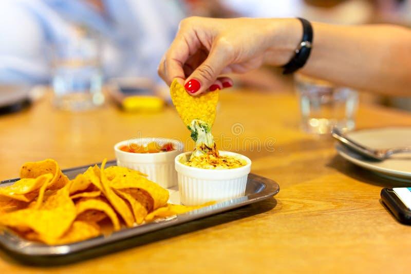 A mão da mulher com o prego da cor vermelha que come uma microplaqueta de tortilha com molho de queijo do nacho no tempo do almoç imagens de stock royalty free